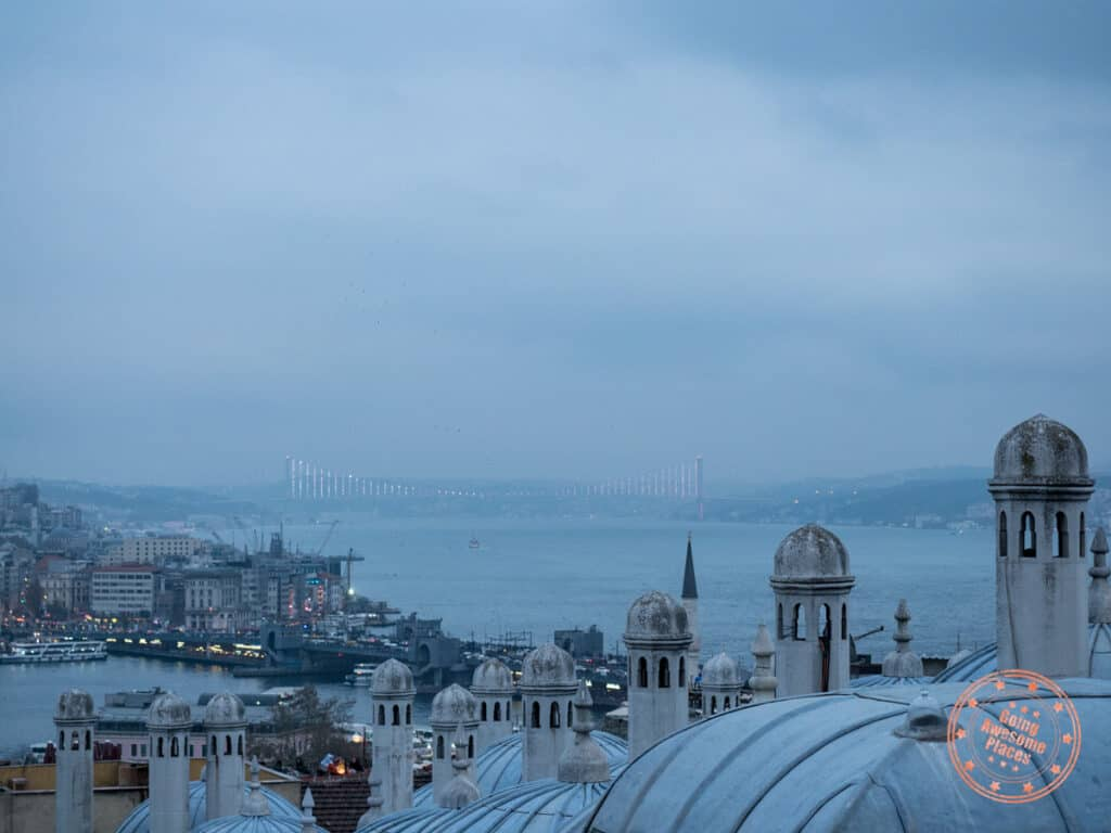 view of rooftops in the foreground and the asia side of istanbul in the background with the bosphorous and bridge at dusk