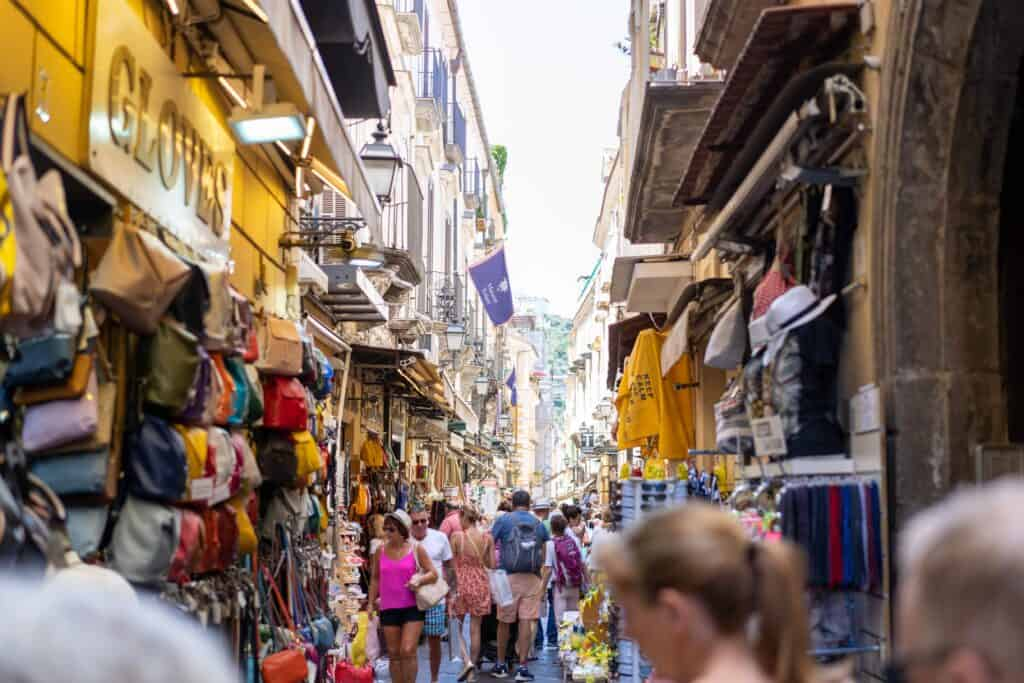 a busy street market with people walking past hats, bags, and clothes in sorrento, italy
