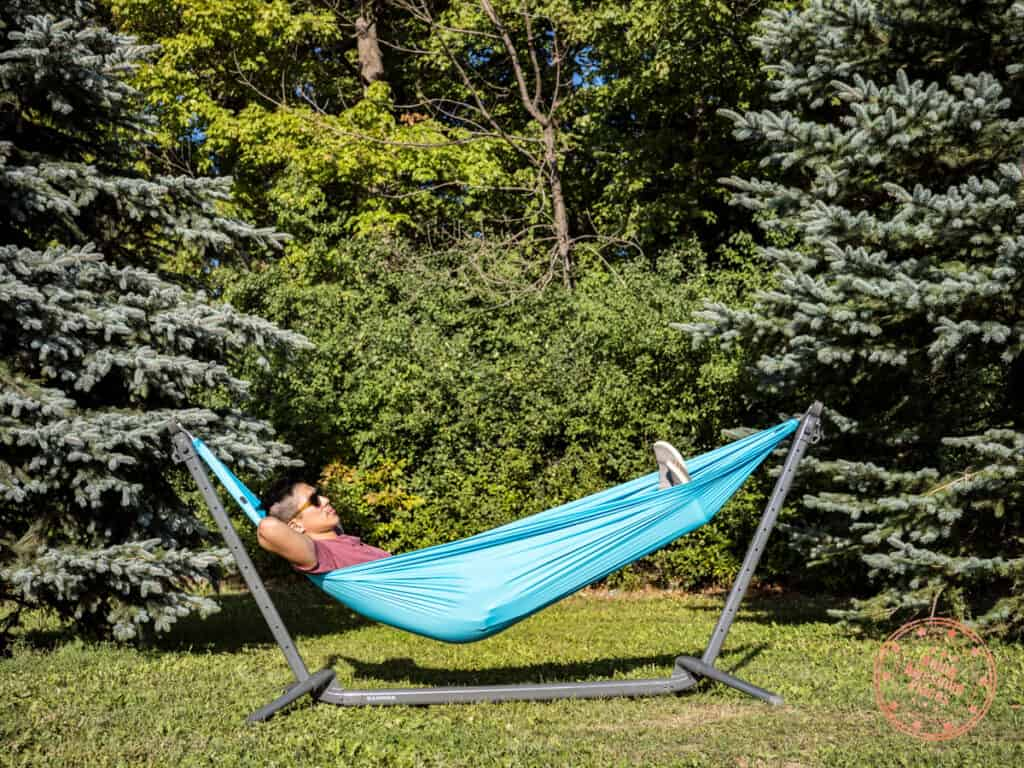man sitting in a kammok roo single attached to a swiftlet portable hammock stand while in the park near trees