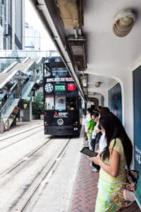 hong kong tramways ding ding on approach with passengers waiting under covered stop