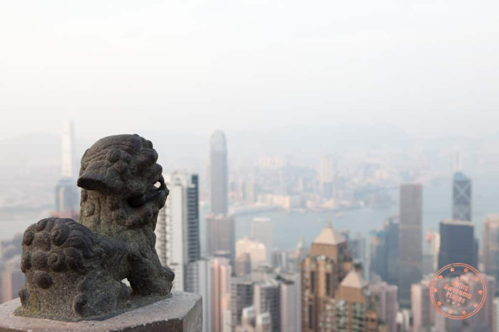 lion statue to the left and the hong kong skyline from victoria peak