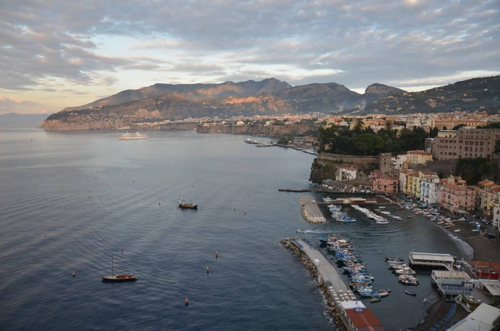 view of the ocean and mountains in the distance of sorrento, italy
