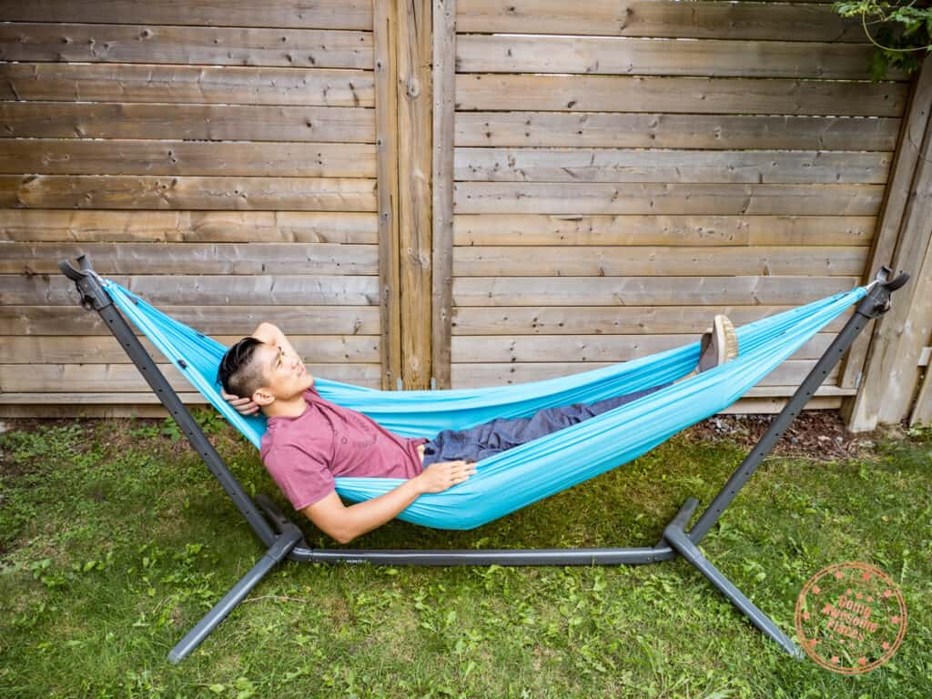 man relaxing on kammok roo single attached to swiftlet in lounge mode