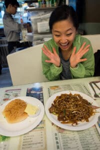 woman extremely excited for breakfast at tsui wah with pineapple bun and beef flat noodles