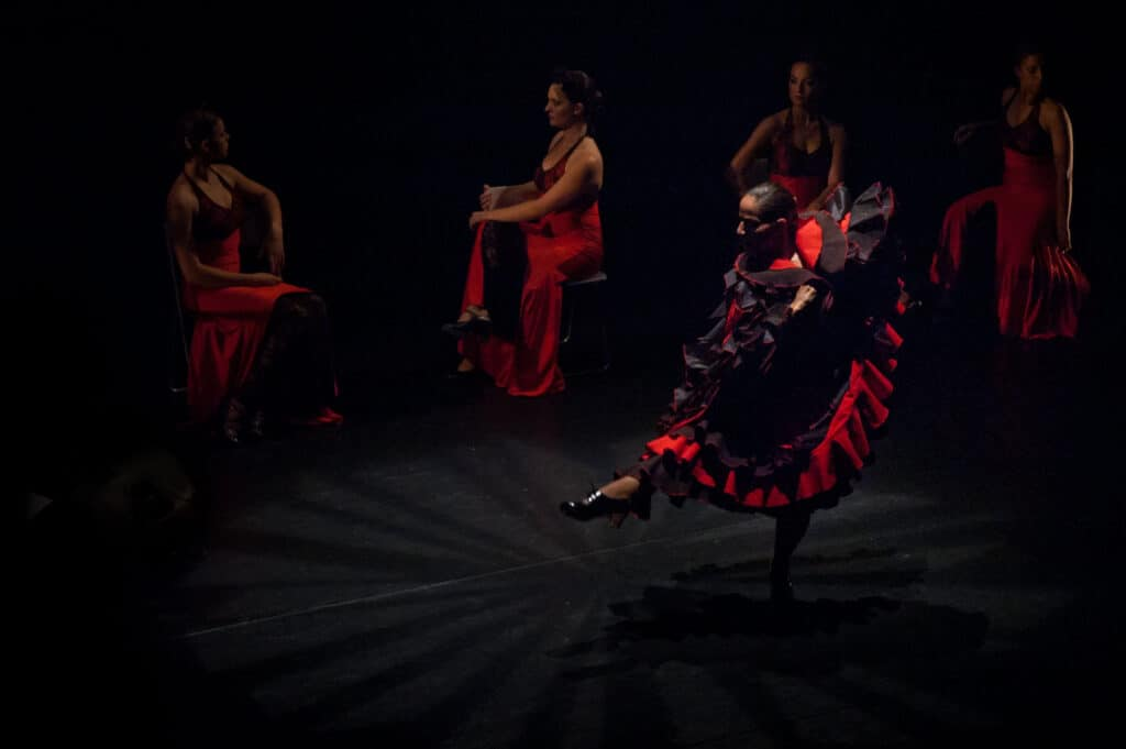 Flamenco dancers in black and red dancing with skirts twirling.