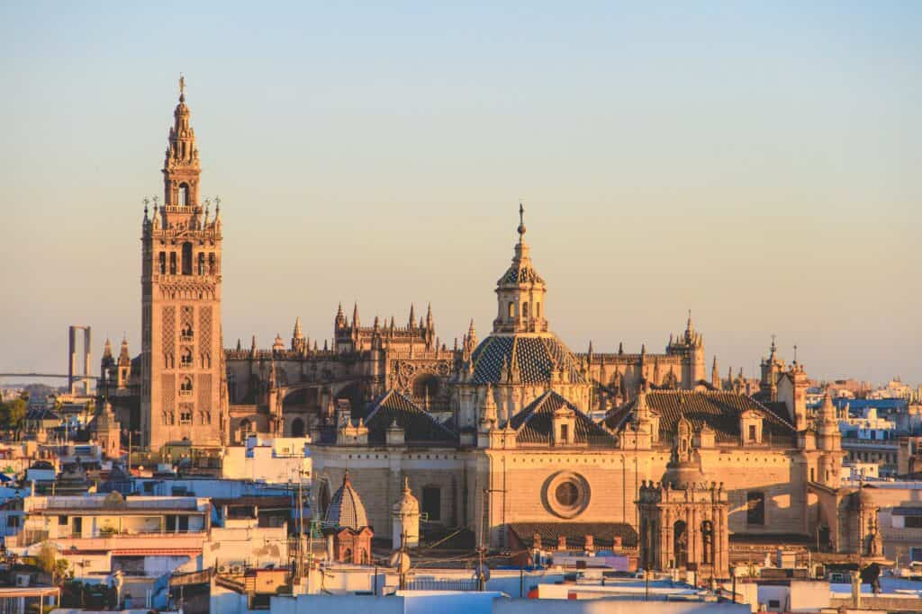 Sunset view of Seville, Spain with many historic buildings.