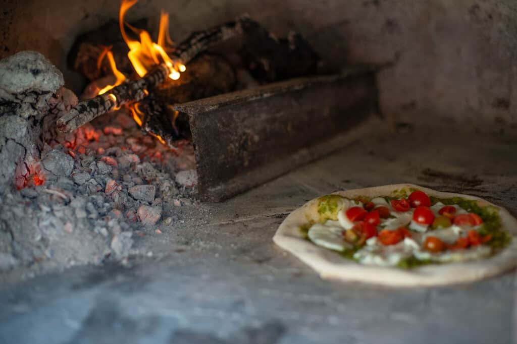 fresh pizza with tomato and mozzarella cooking in a wood fire oven.