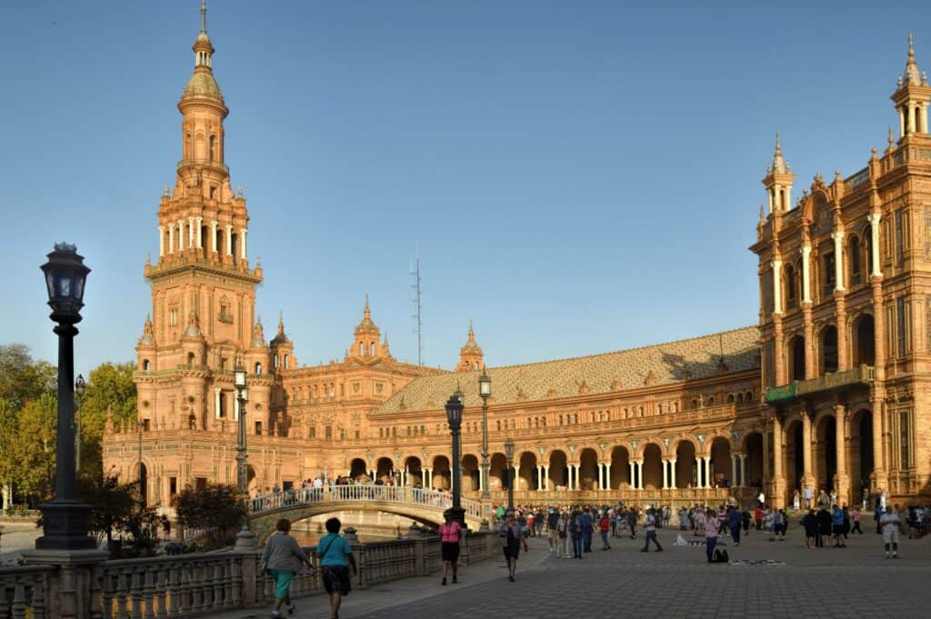 The Plaza de Espana with many people walking along the plaza in front in Seville, Spain.