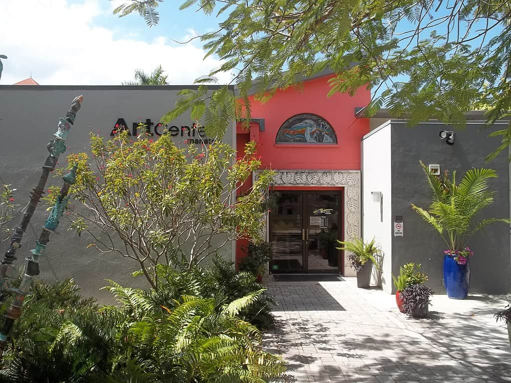 the front of the art center manatee building with a bright red door and palm trees outside