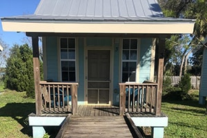 small blue cabin with a porch at jiggs landing lakefront cabins
