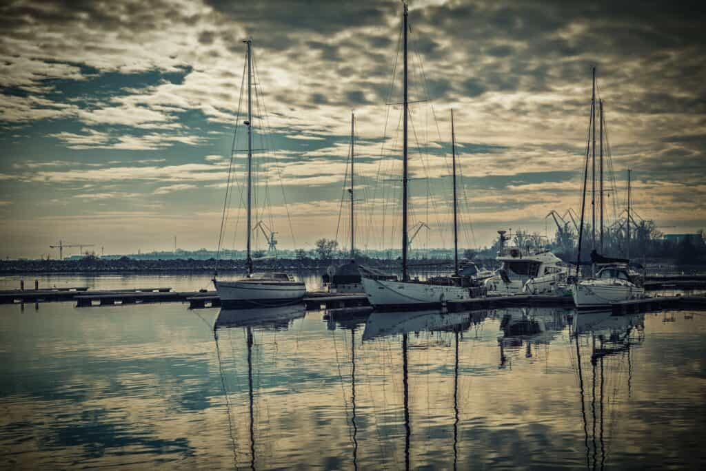 several sailboats floating in still water that is reflecting clouds
