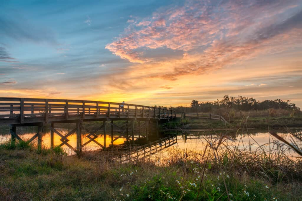 a long wooden bridge over a river with the sunsetting in the background