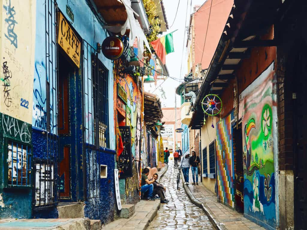 looking down a street in bogota with graffiti walls and people walking on cobblestone