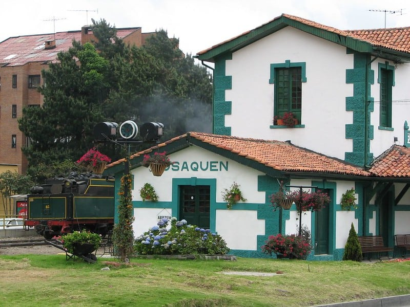 white and green old train station with a train out from and hanging flowers in usaquen