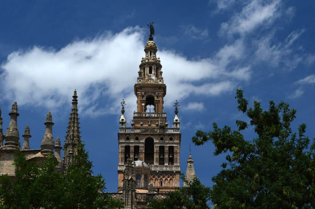 The Giralda Tower in Los Remedios against a blue sky with trees surrounding