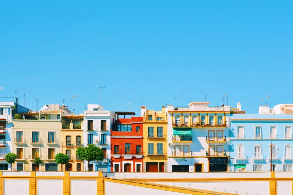 A row of colorful buildings along a street in the Triana neigborhood in Seville.