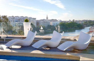 Rooftop chairs beside a glass wall overlooking the river in Triana, Seville, Spain.