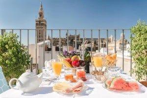 A table set with breakfast on a sunny morning on the rooftop of the Hotel Casa de Colon in Seville