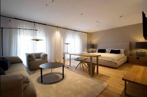 Large, modern hotel room with a bed, chair and couch at the Hotel Zenit Sevilla