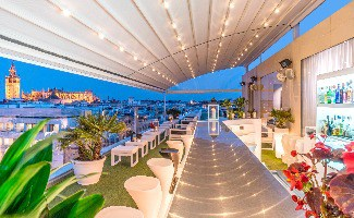 A rooftop patio lit up at night over looking the city in Seville, Spain