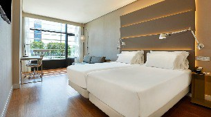 A spacious hotel room with a view of the city of Seville at the NH Sevilla Plaza de Armas hotel