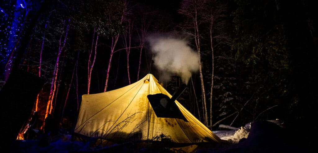 temagami outfitting co winter backcountry adventure tent with fireplace at night