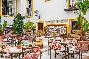 A courtyard with tables and chairs at the Vincci La Rabida Hotel in Seville, Spain