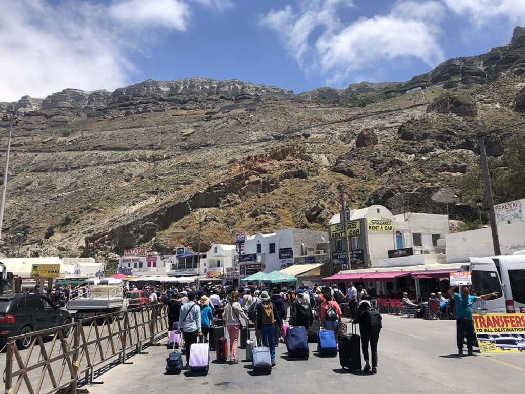 arriving at athinios ferry port in santorini with car rental companies on the right