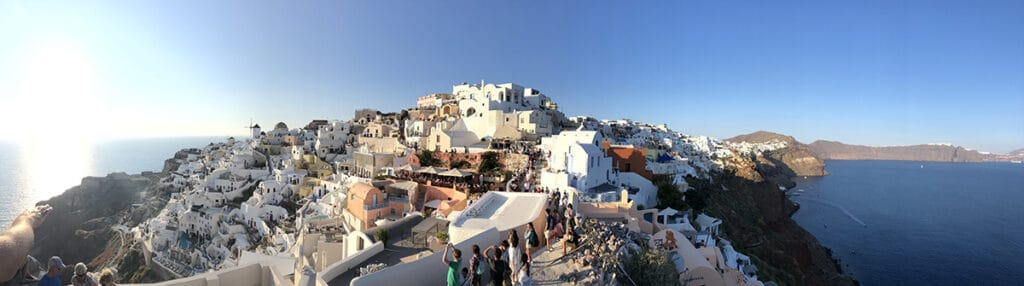 panorama of oia crowds at sunset in santorini
