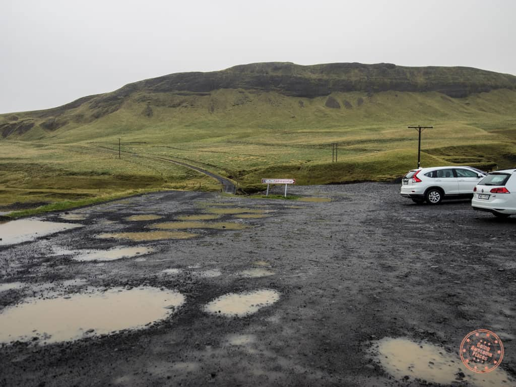the gravel parking lot at fjadragljufur canyon with lots of pot holes filled with water